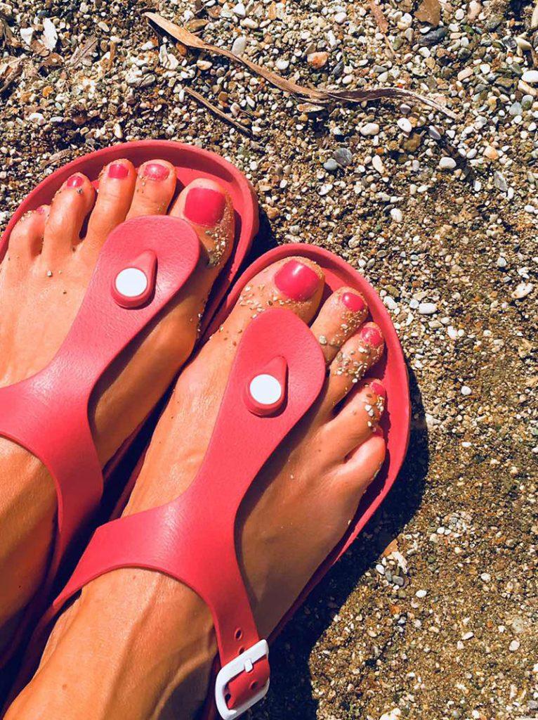 дамски крака с червен лак и червени гумени сандали BIRKENSTOCK на морския пясък