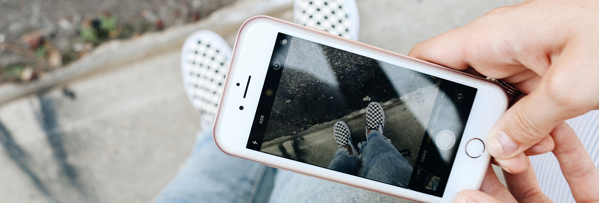 човек снимка обувките си на улицата с телефон