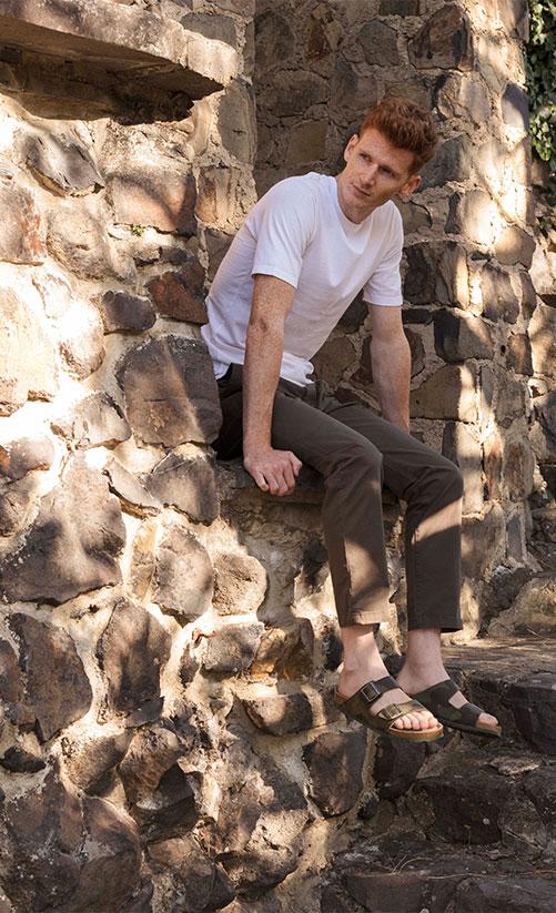 млад мъж с чехли BIRKENSTOCK седнал на каменна ограда