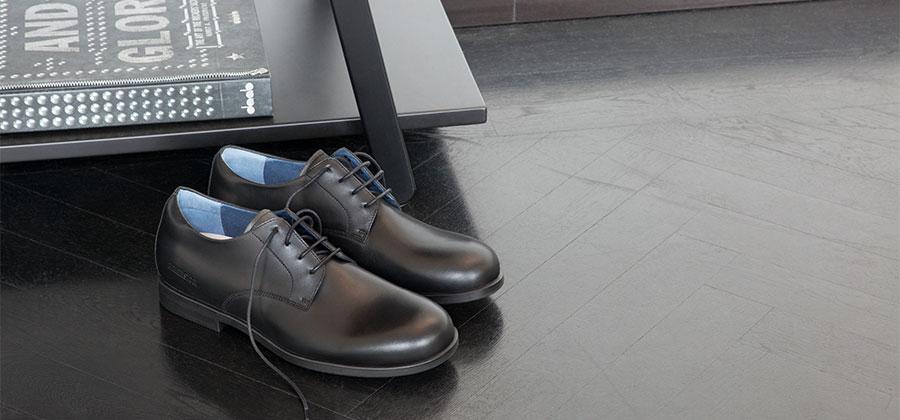 черни мъжки обувки BIRKENSTOCK върху тъмен под