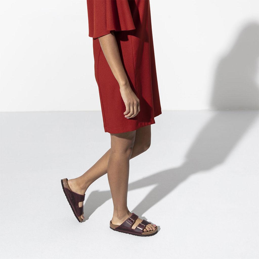 женски крака с червена рокля и чифт дамски винено червени кожени чехли Биркенщок / BIRKENSTOCK Arizona SFB FL Zinfandel