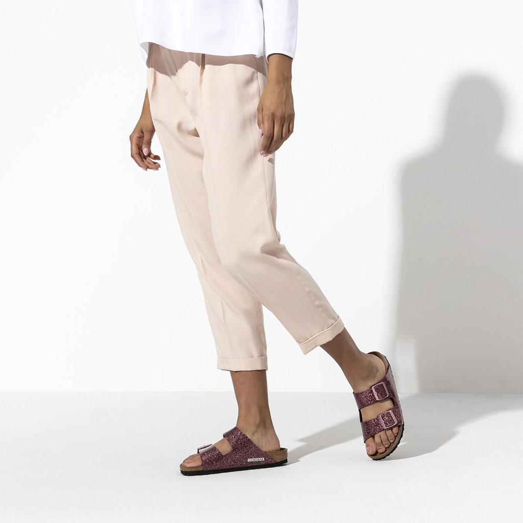 чифт дамски чехли Биркенщок / BIRKENSTOCK Arizona BF блестящо червени обути на дамски крака със светъл панталон